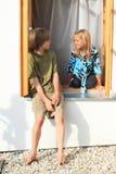 Flicka och pojke på fönstret Arkivbild