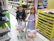 Flicka och pojke på supermarket royaltyfri fotografi