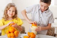 Flicka och pojke sammanpressad ny fruktsaft Fotografering för Bildbyråer