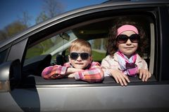 Flicka och pojke som kör faderbilen Royaltyfria Foton
