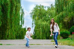 Flicka och pojke som spelar badminton i parkera Arkivbild