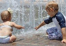 Flicka och pojke som spelar i ett färgstänkblock Arkivbilder