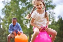 Flicka och pojke som spelar med spacehooper Arkivbilder