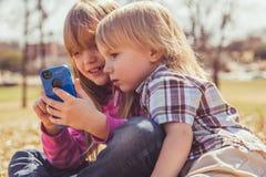 Flicka och pojke som spelar med telefonen Arkivbilder