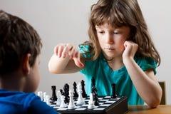 Flicka och pojke som spelar schack Royaltyfri Foto