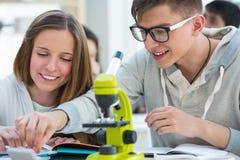 Flicka och pojke som tillsammans arbetar på biologi Arkivfoto