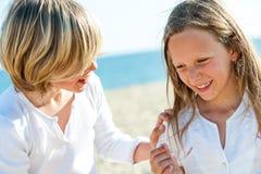 Flicka och pojke som tillsammans skrattar. Royaltyfria Foton