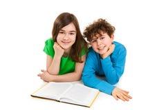 Flicka- och pojkeläsebok som ligger Royaltyfri Fotografi