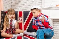 Flicka- och pojkesammanträde på stol med en brittisk flagga arkivbild