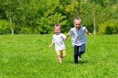 Flicka- och pojkespring på gräset Fotografering för Bildbyråer