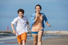 Flicka- och pojkespring på stranden Royaltyfri Fotografi