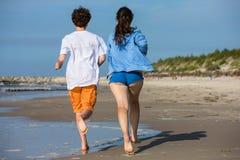 Flicka- och pojkespring på stranden Arkivfoto