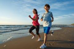 Flicka- och pojkespring på stranden Royaltyfri Bild