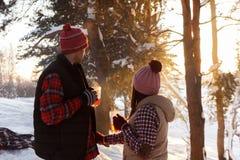 Flicka och pojkvän som dricker från händer för ett koppinnehav i vinter i skogen arkivbilder