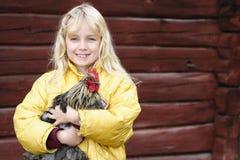 Flicka och rooster Arkivfoto