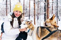 Flicka och skrovlig hundkapplöpning i släden Finland i Lapland i vinter arkivbild