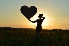 Flicka och solnedgång arkivfoto