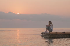 Flicka och soluppgång över havet Fotografering för Bildbyråer