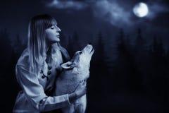 Flicka och varg i den djupa skogen Arkivfoto