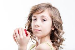 Flicka omkring som biter ett rött äpple på vit bakgrund Royaltyfri Bild