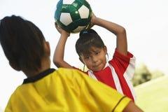 Flicka omkring som kastar fotbollbollen arkivbild