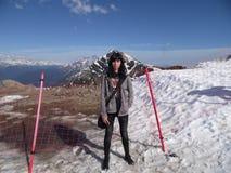 Flicka på överkanten av berget, de snöig maxima och den blåa himlen Royaltyfri Bild