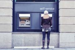 Flicka på ATM royaltyfri bild