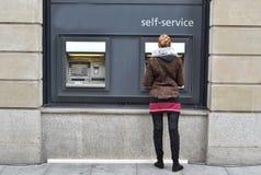 Flicka på ATM royaltyfria foton