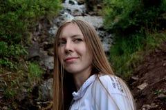 Flicka på bakgrunden av en vattenfall arkivfoton
