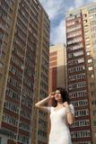 flicka på bakgrunden av mång--våning byggnader arkivbilder