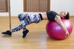 Flicka på bollen i idrottshallen som gör övningar royaltyfria foton