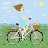 Flicka på cykelflicka på cykeln på bakgrund av havet Arkivfoto