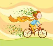 Flicka på cykeln, höstbakgrund Fotografering för Bildbyråer