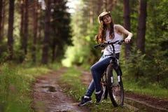 Flicka på cykeln på skogen Arkivfoton