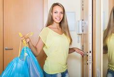 Flicka på dörren med avfallpåsar royaltyfri foto