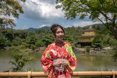 Flicka på den guld- paviljongen - Kyoto, Japan Arkivfoto