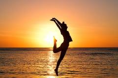 Flicka på den guld- solnedgången på stranden arkivfoton
