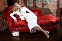 Flicka på den röda soffan royaltyfri bild