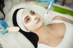 Flicka på den Spa salongen KosmetologApplying White Cosmetic pulver Arkivfoton