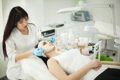 Flicka på den Spa salongen KosmetologApplying White Cosmetic pulver Royaltyfri Bild