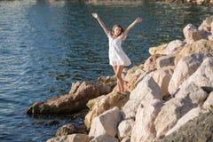 Flicka på den steniga kusten i solig dag arkivbild