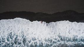 Flicka på den svarta sandstranden royaltyfria bilder
