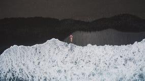 Flicka på den svarta sandstranden royaltyfri fotografi