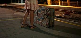 Flicka på drevstationen med resväskan under natt Arkivbilder