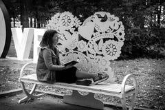 Flicka på en bänk i parkera med en bok i hennes händer, svartvitt foto royaltyfri foto