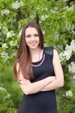 Flicka på en bakgrund av ett blomstra träd arkivfoton