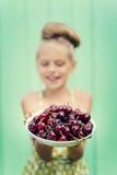 Flicka på en bakgrund av plattan för turkosvägginnehav med körsbäret fotografering för bildbyråer