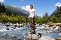 Flicka på en bergflod Arkivfoto
