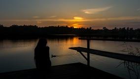 Flicka på en bro under solnedgång arkivfoto
