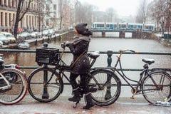 Flicka på en cykel på bron arkivbild